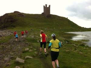 Runners approach Dunstanburgh castle