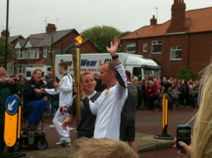 Michael Moore takes the Olympic flame from Jonny Miller