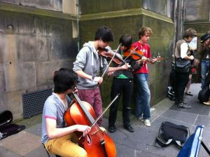 Young boys playing cello and fiddles on the street